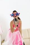Junges Mädchen mit lustigen Gläsern singend Lizenzfreies Stockfoto