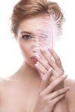 Junges Mädchen mit Make-upakt und rosa Feder in den Händen Schönes Modell mit einer leichten Maniküre stockfoto