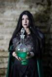 Junges Mädchen mit Pelzkap und Flasche mit Trank Aussehen wie Halloween-Klage Stockbild