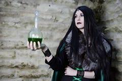 Junges Mädchen mit Pelzkap und Flasche mit Trank Aussehen wie Halloween-Klage Stockfotografie