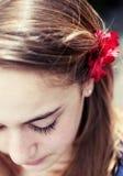 Junges Mädchen mit roter Blume auf ihrem Haar Stockfotos