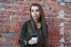 Junges Mädchen mit trinkendem Kaffee des langen Haares Lizenzfreie Stockbilder