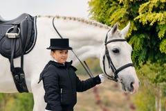 Junges Mädchen mit weißem Dressurreitenpferd Lizenzfreies Stockbild