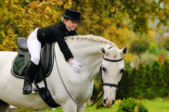 Junges Mädchen mit weißem Dressurreitenpferd Stockfotografie