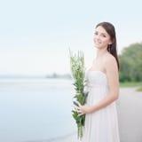 Junges Mädchen mit weißen Blumen auf dem Strand Stockfotografie