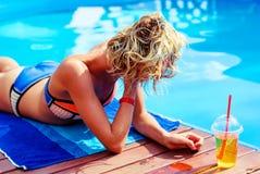 Junges Mädchen nahe dem Pool mit einem Cocktail Lizenzfreie Stockbilder