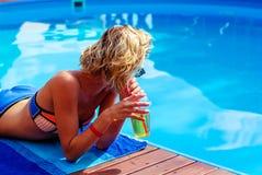 Junges Mädchen nahe dem Pool mit einem Cocktail Stockfoto