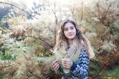 Junges Mädchen nahe einem Nadelbaum stockfoto