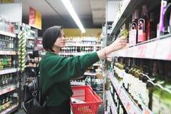 Junges Mädchen nimmt Wein vom Supermarktregal Der Käufer kauft Alkohol im Speicher Einkauf im Supermarkt Stockfoto