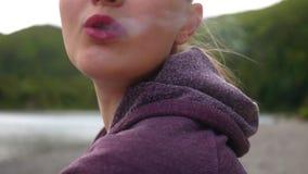 Junges Mädchen rauchendes vape in der Natur und Schlagrauch in die Kamera stock video footage