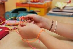 Junges Mädchen ` s übergibt das Spinnen einer Plastikarmbandnahaufnahme Stockfotos