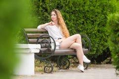 Junges Mädchen schaut auf den Seiten, die auf einer Parkbank stillstehen Stockfotografie