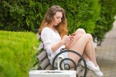 Junges Mädchen schreibt eine Mitteilung am Telefon, auf einer Parkbank Stockfotografie