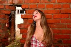 Junges Mädchen schreit über eine Backsteinmauer Lizenzfreie Stockfotografie