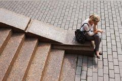Junges Mädchen sitzt auf den Granitjobsteps lizenzfreies stockbild