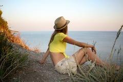 Junges Mädchen sitzt auf einer wilden steinigen Seeküste und betrachtet Meer bei Sonnenuntergang Stockfotos