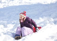 Junges Mädchen spielt mit dem Rodeln auf Schnee im Winter im moun Stockfotografie