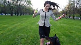 Junges Mädchen spielt mit einem Hund im Park stock video footage
