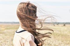 Junges Mädchen steht auf dem Gebiet und Wind flattert ihr Haar Stockfoto