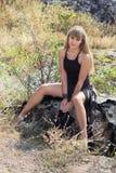 Junges Mädchen steht auf einem großen Felsen still Stockfotos
