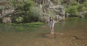 Junges Mädchen steht den Knöchel, der auf einem Felsen in einem Fluss dann aufprallt tief ist dann, auf und ab stock video footage