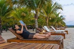 Junges Mädchen Tablette auf dem Strandurlaubsort sich entspannen und benutzen lizenzfreie stockfotografie