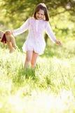 Junges Mädchen-tragender Teddybär auf dem Gebiet Stockfoto