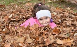 Junges Mädchen und der Herbstlaub Lizenzfreie Stockfotos