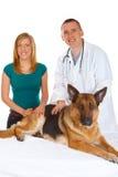Junges Mädchen und ein Tierarzt, der ihren Hund überprüft stockfotografie
