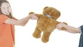 Junges Mädchen und Junge, die über Bären kämpft Stockbild