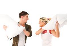 Junges Mädchen und Junge, die einen Kissenkampf hat Stockbilder