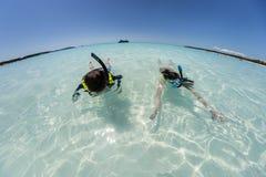 Junges Mädchen und Junge, die im haarscharfen Wasser mit Kreuzschiff im Hintergrund mit gebogenem Weitwinkelhorizont schnorchelt stockfotografie