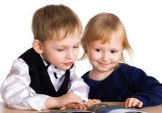 Junges Mädchen und Junge schauen das Buch Lizenzfreie Stockbilder