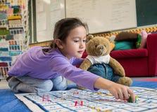 Junges Mädchen und Teddy Playing Snakes und Leitern stockfotografie