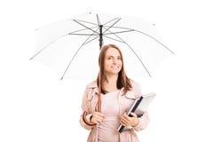 Junges Mädchen unter einem Regenschirm, der einige Notizbücher trägt stockbild