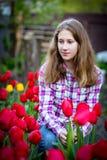 Junges Mädchen unter roten Tulpen Lizenzfreies Stockbild