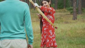 Junges Mädchen visieren ihren Bogen auf Mann an stock footage