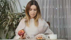 Junges Mädchen wählen die Heilung zwischen Pillen und einem Apfel stock footage