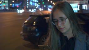 Junges Mädchen, welches das Telefon auf dem Hintergrund der Nachtstadt betrachtet stock video footage