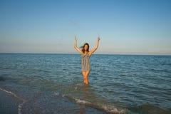 Junges Mädchen, welches das Wasser im Meer spritzt Stockfotografie