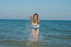 Junges Mädchen, welches das Wasser im Meer spritzt Lizenzfreies Stockfoto