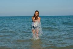 Junges Mädchen, welches das Wasser im Meer spritzt Lizenzfreies Stockbild
