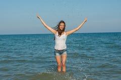Junges Mädchen, welches das Wasser im Meer spritzt Stockfoto