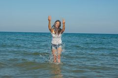 Junges Mädchen, welches das Wasser im Meer spritzt Lizenzfreie Stockbilder