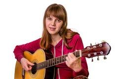 Junges Mädchen, welches die Akustikgitarre - lokalisiert auf Weiß spielt Lizenzfreie Stockfotografie