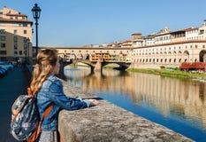 Junges Mädchen, welches die Ansicht von Ponte Vecchio in Florenz genießt Lizenzfreies Stockfoto
