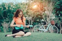 Junges Mädchen, welches die Musikukulele im Freien spielt lizenzfreie stockbilder