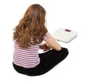 Junges Mädchen, welches die Skala betrachtet Lizenzfreies Stockfoto