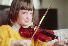 Junges Mädchen, welches die Violine lächelt an der Kamera spielt Lizenzfreies Stockbild
