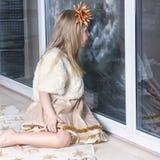 Junges Mädchen, welches heraus das Fenster schaut stockfotos